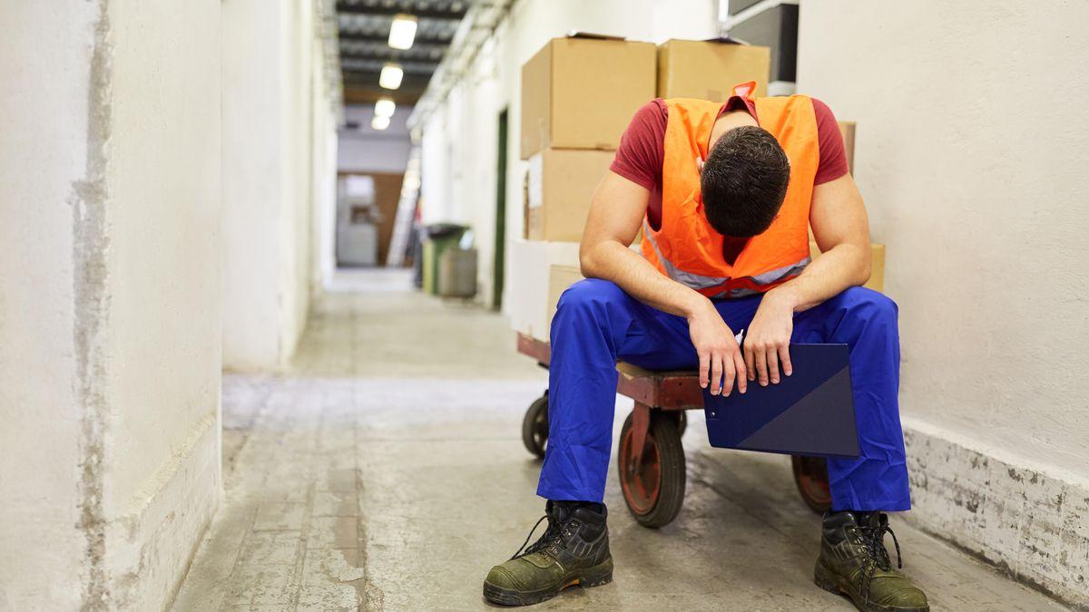 Arbeiter sitzt erschöpft auf einem Schubwagen im Warenlager wegen Überstunden.