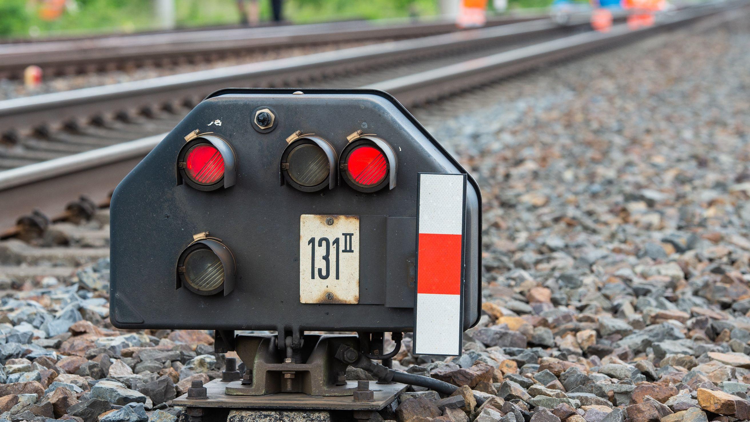 Signal an Bahnstrecke steht auf Rot, im Hintergrund Arbeiter in orangefarbener Kleidung (Symbolbild).