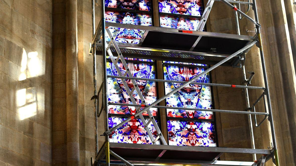 In einem alten Kirchenfenster kann man hinter einem Gerüst die neuen Fenster von Gerhard Richter erahnen.