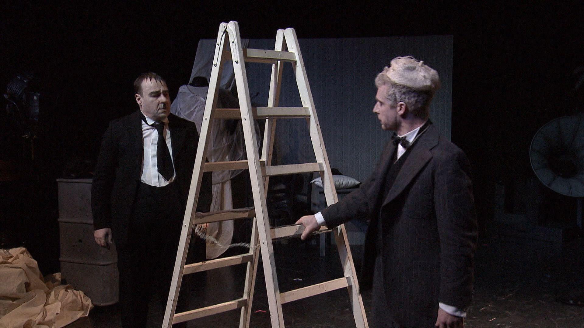 Zwei Schauspieler stehen auf der Bühne, dazwischen eine Leiter