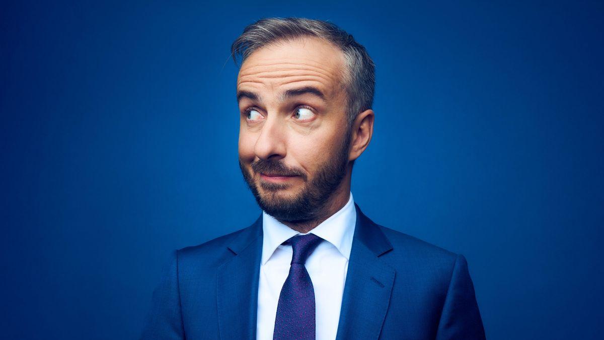 Vor blauem Hintergrund im blauen Anzug