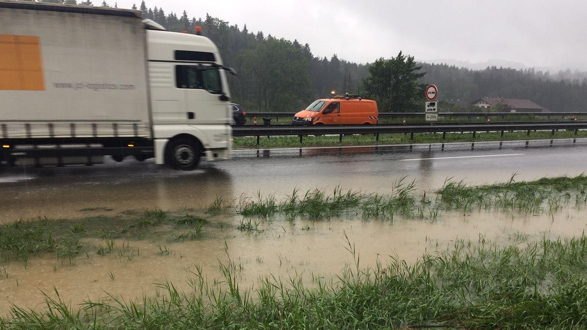 LKW fährt über teilweise überschwemmte Fahrbahnen der A8