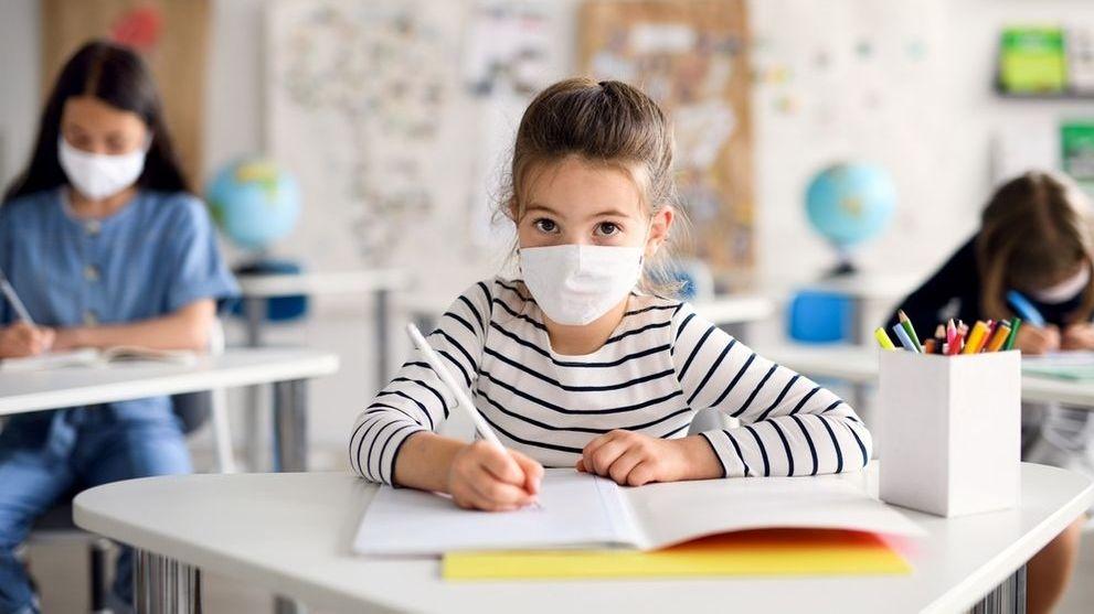 Ein Schulkind mit Maske im Unterricht. Strenge Hygieneregeln helfen bei der Corona-Pandemie.
