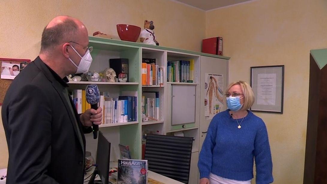 BR-Reporter Markus Feulner interviewt Hausärztin Petra Reis-Berkowicz, beide tragen Mundschutz.