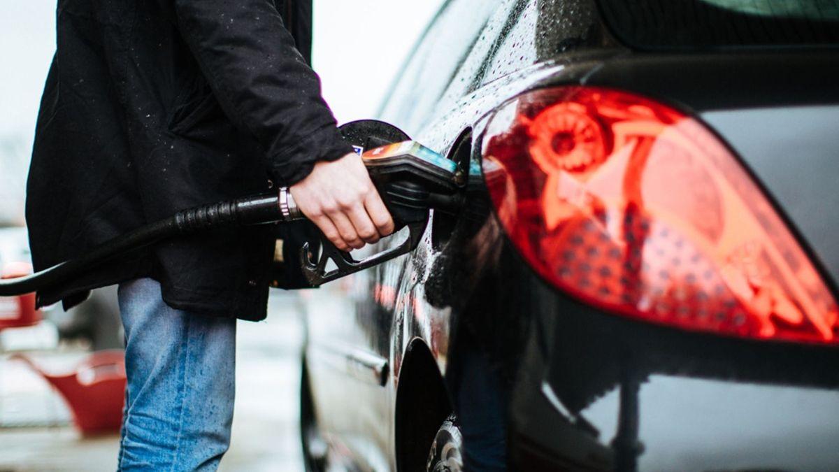 Ein Mann in schwarzer Jacke steckt die Tankpistole in den Tankstutzen seines Autos und tankt.