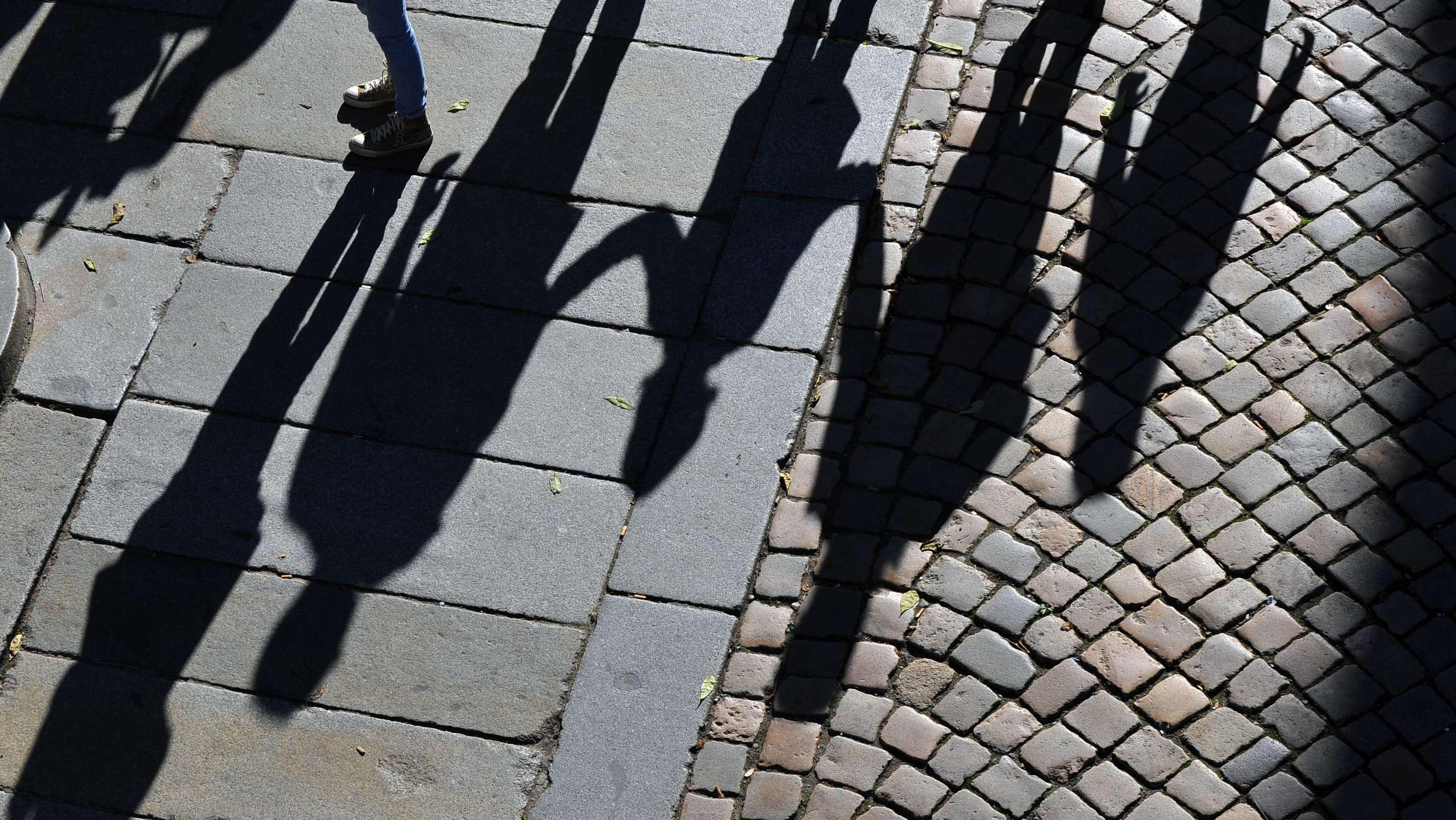 Symbolbild: Schatten von Personen unterschiedlichen Alters auf dem Asphalt
