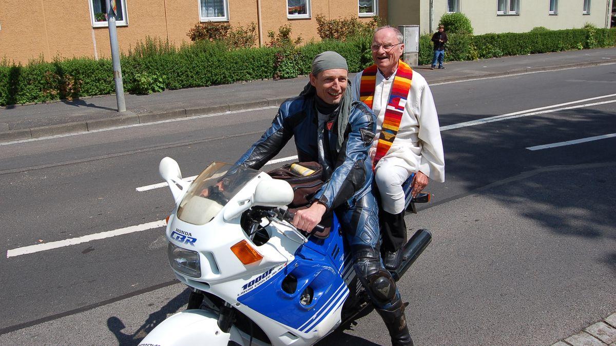 Pfarrer Breitenbach sitzt bei einem Mann auf dem Motorrad.
