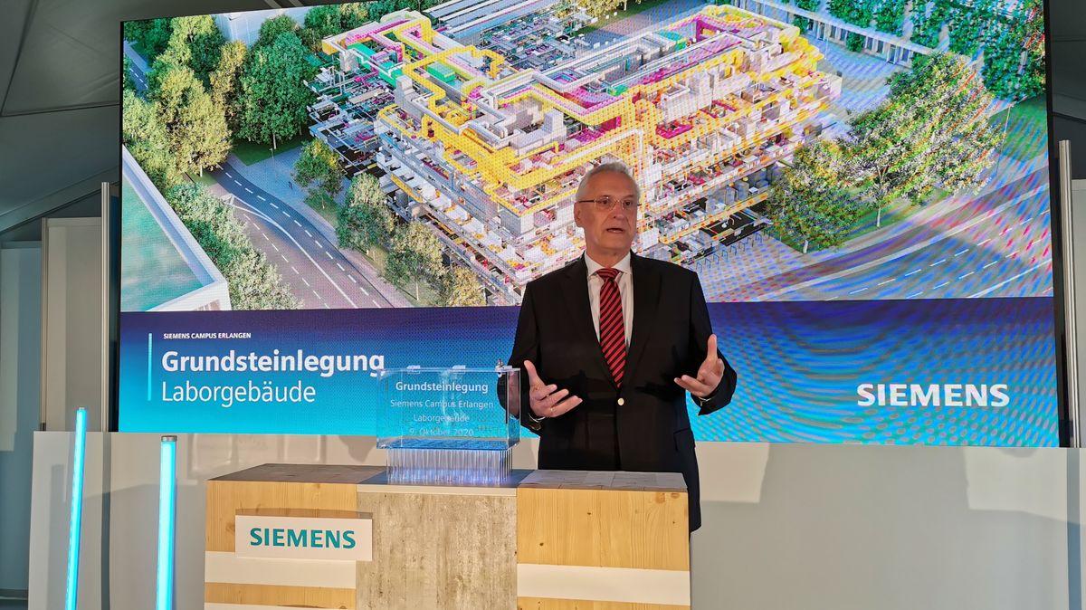 Joachim Herrmann vor einer Videoleinwand bei der Grundsteinlegung zum neuen Laborgebäude.