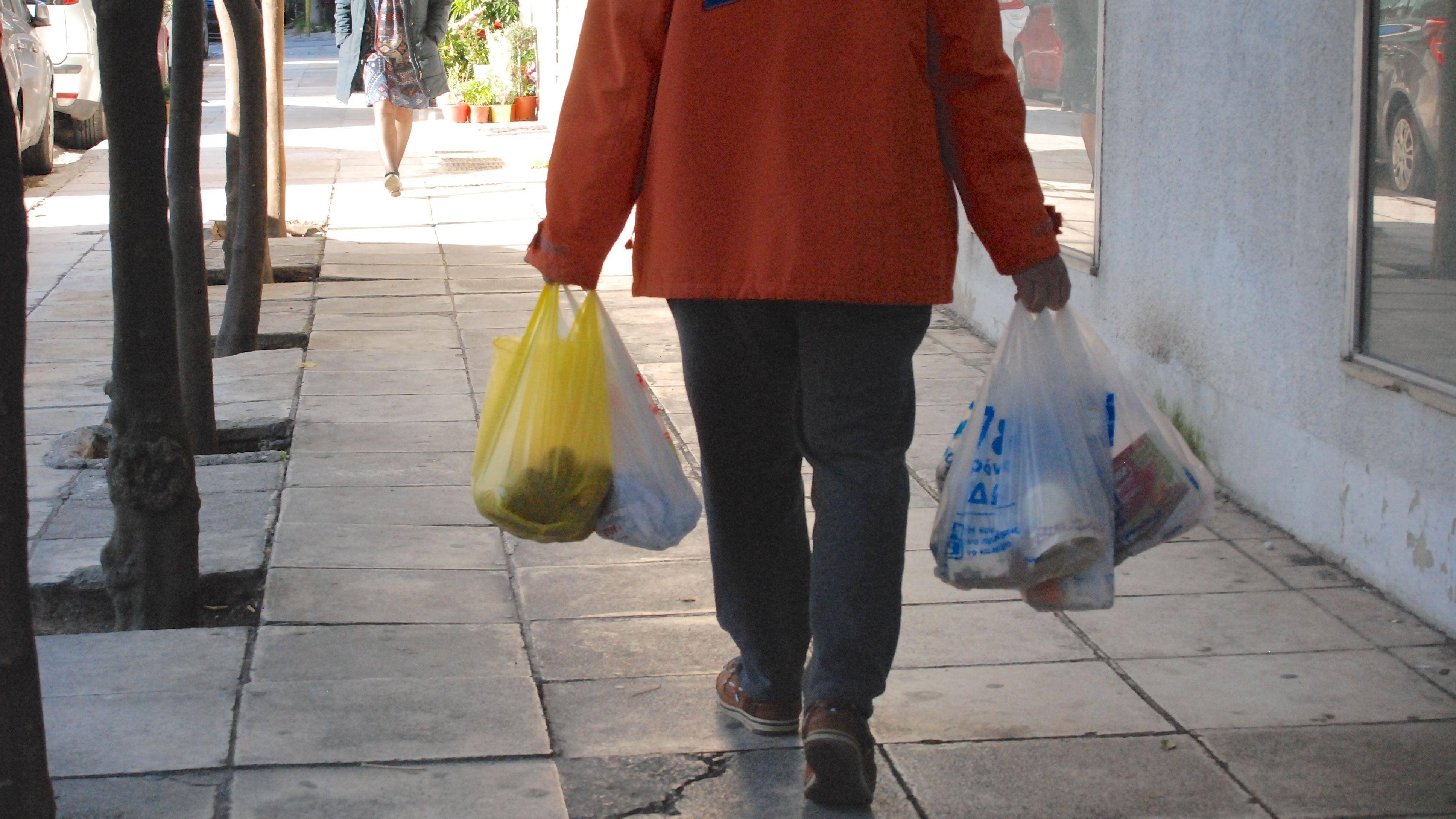 Mann trägt Plastiktüten