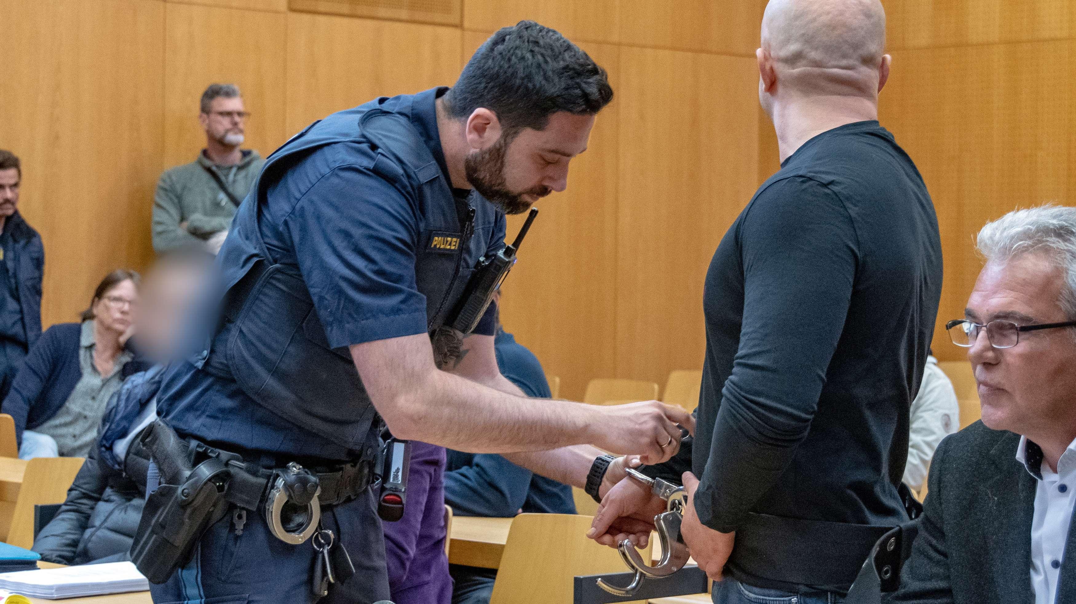 Einem Angeklagten der Schmugglerbande werden im Verhandlungssaal des Landgerichts Landshut die Handschellen abgenommen.