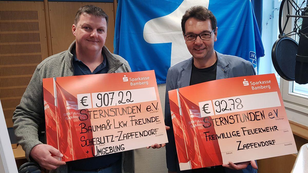 Tino Schütz (links) mit Bayern1-Moderator Jürgen Lassauer bei der Übergabe der Spenden für Sternstunden