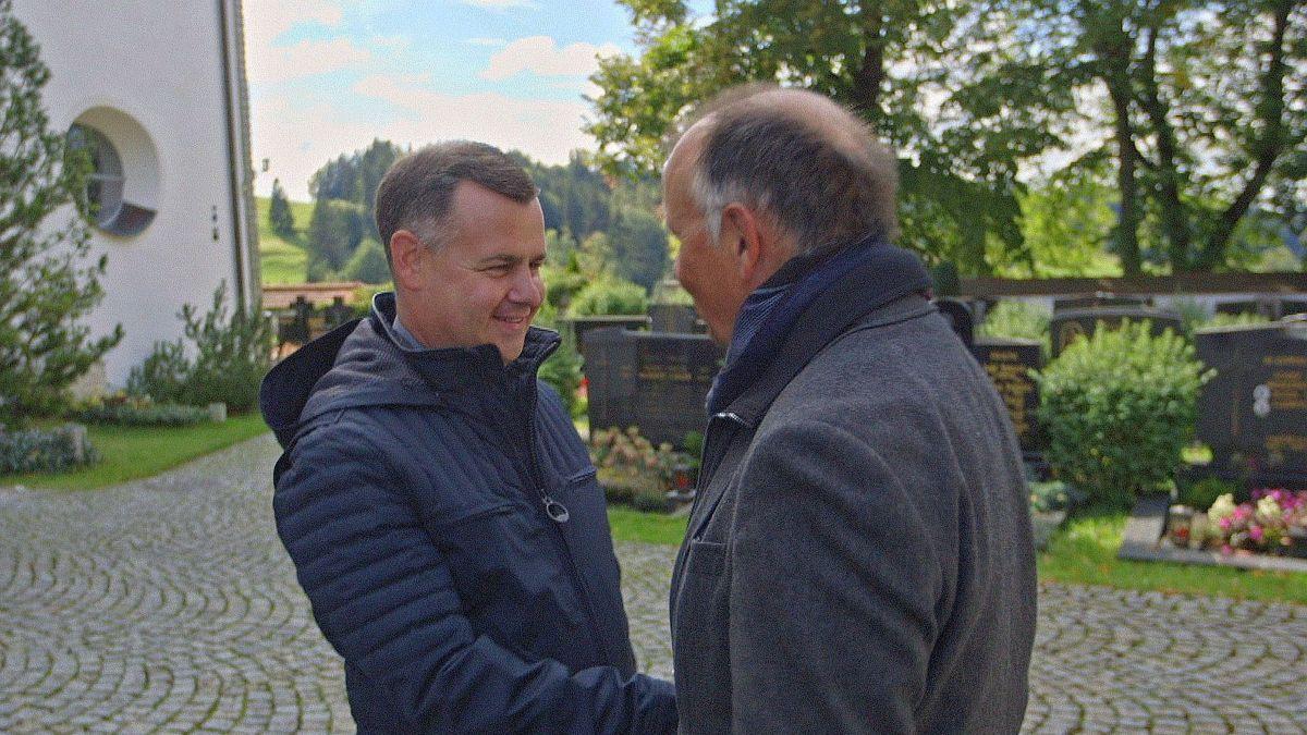 Pfarrer Wolfgang Schnabel und sein Bruder Ralf begrüßen sich vor der Kirche.