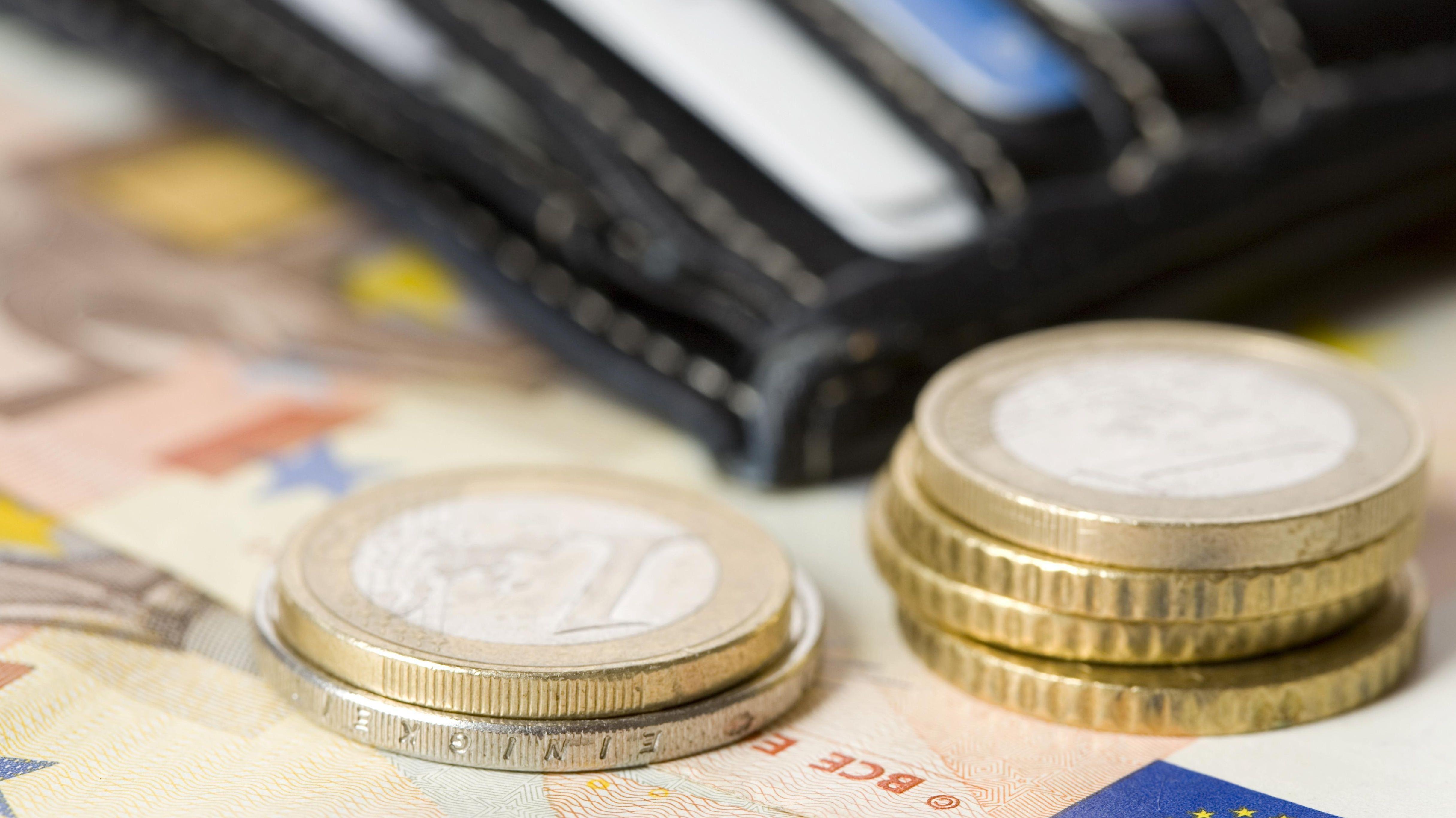 Ein Geldbeutel mit Münzen und Scheinen im Vordergrund.
