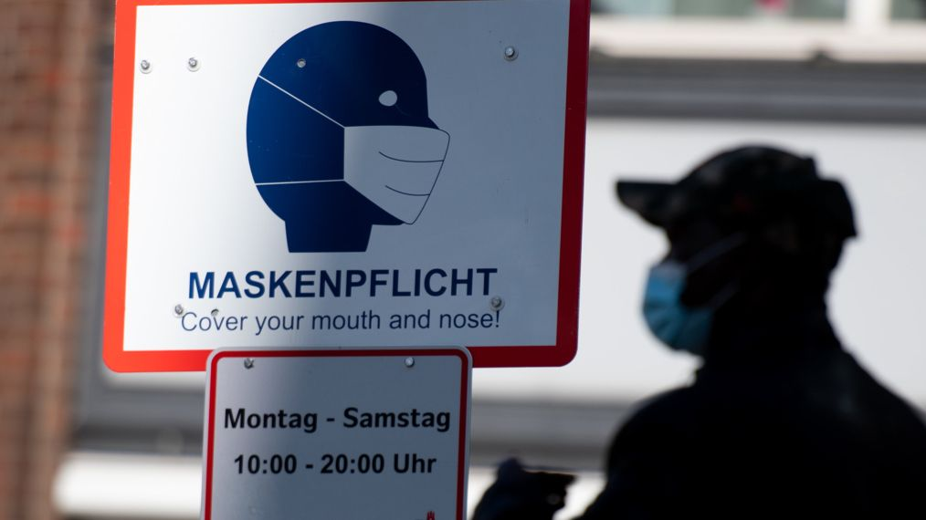 """in Mann geht in der Innenstadt an einem Schild mit der Aufschrift """"Maskenpflicht"""" vorbei."""