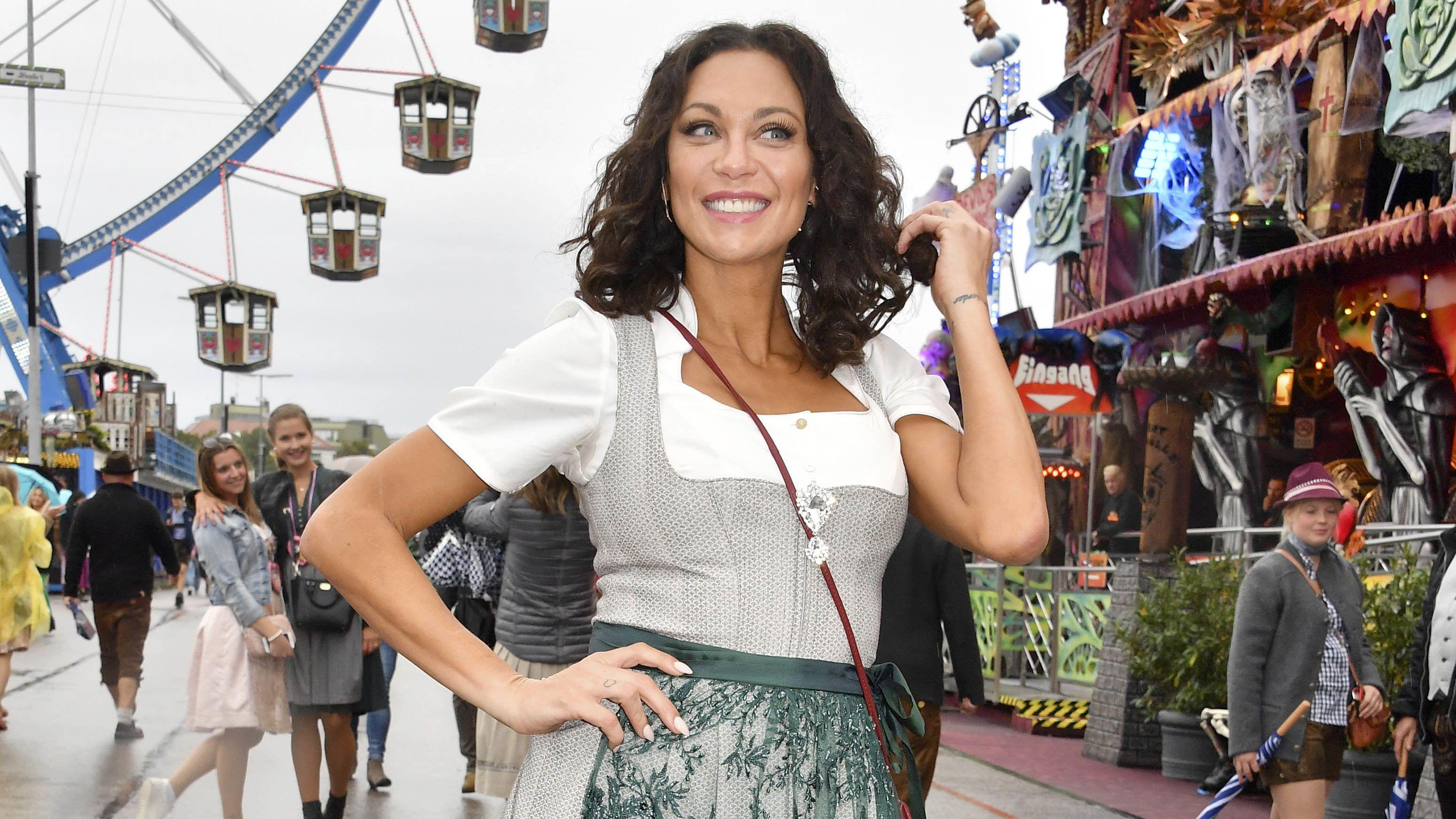 Lilly Becker posiert im Dirndl 2019 vor Riesenrad und Buden auf dem Oktoberfest