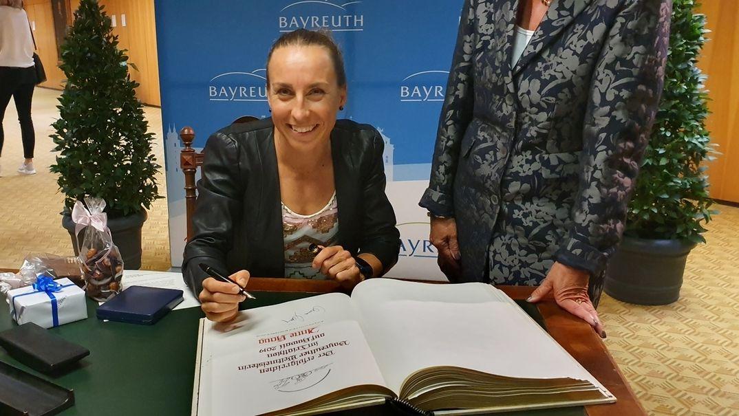 Anne Haug sitzt mit einem Stift in der rechten Hand vor dem Goldenen Buch der Stadt Bayreuth.