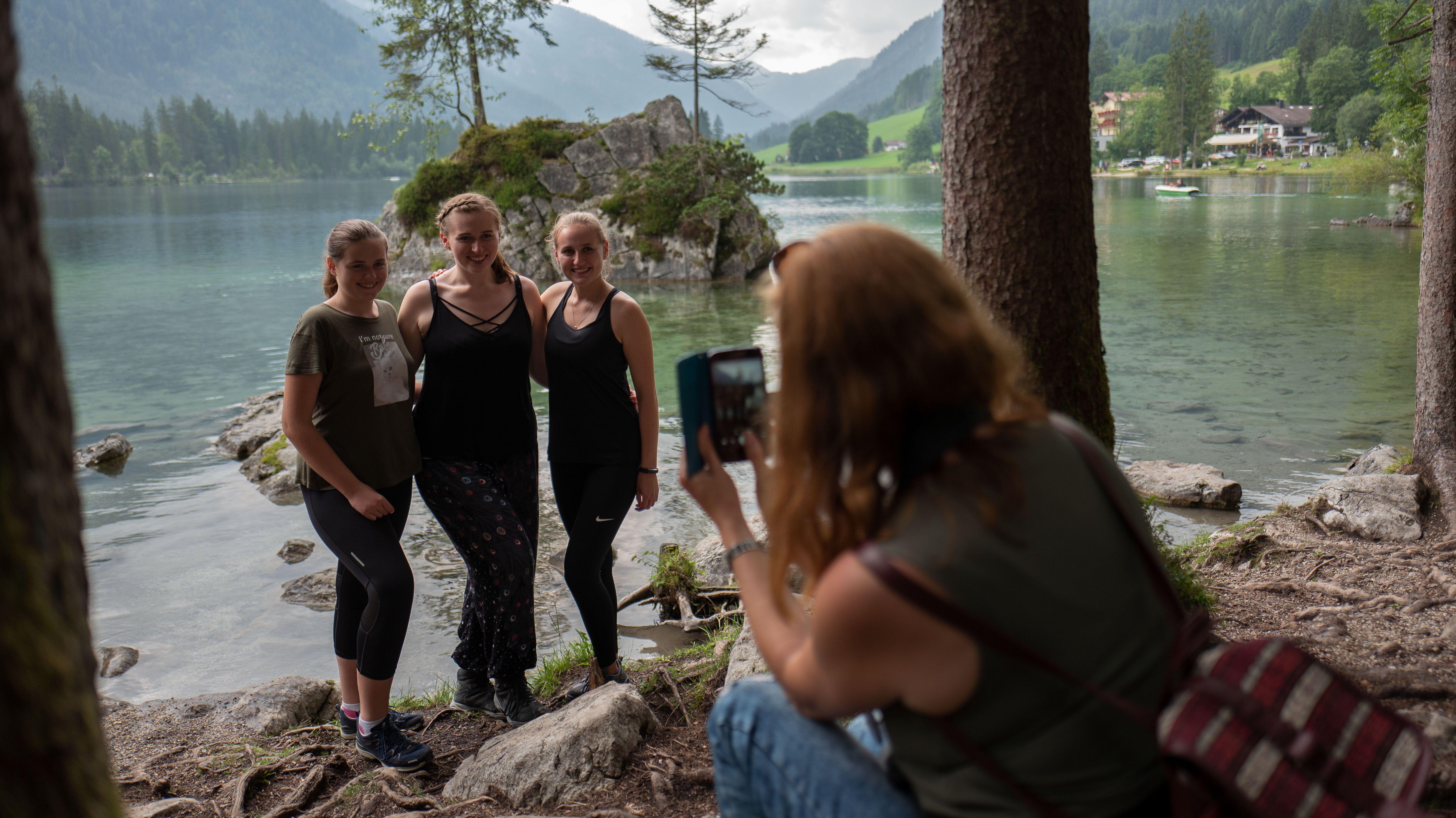 Drei Freundinnen lassen sich am Ufer des Hintersees fotografieren.
