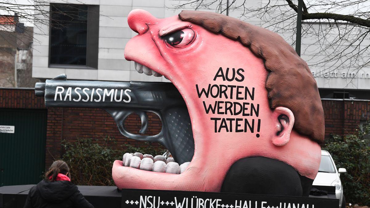 """Ein Motivwagen """"Rassismus - Aus Worten werden Taten! +++ NSU +++ W. Lübcke +++ Halle +++ Hanau"""" steht vor dem Rosenmontagszug auf der Straße."""