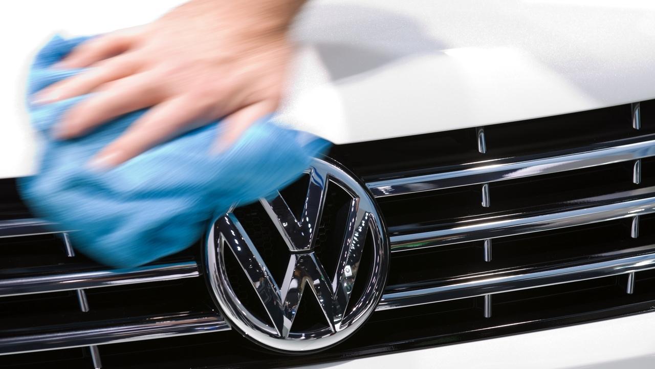 Eine Hand wischt mit einem Tuch über die Motorhaube eines VW