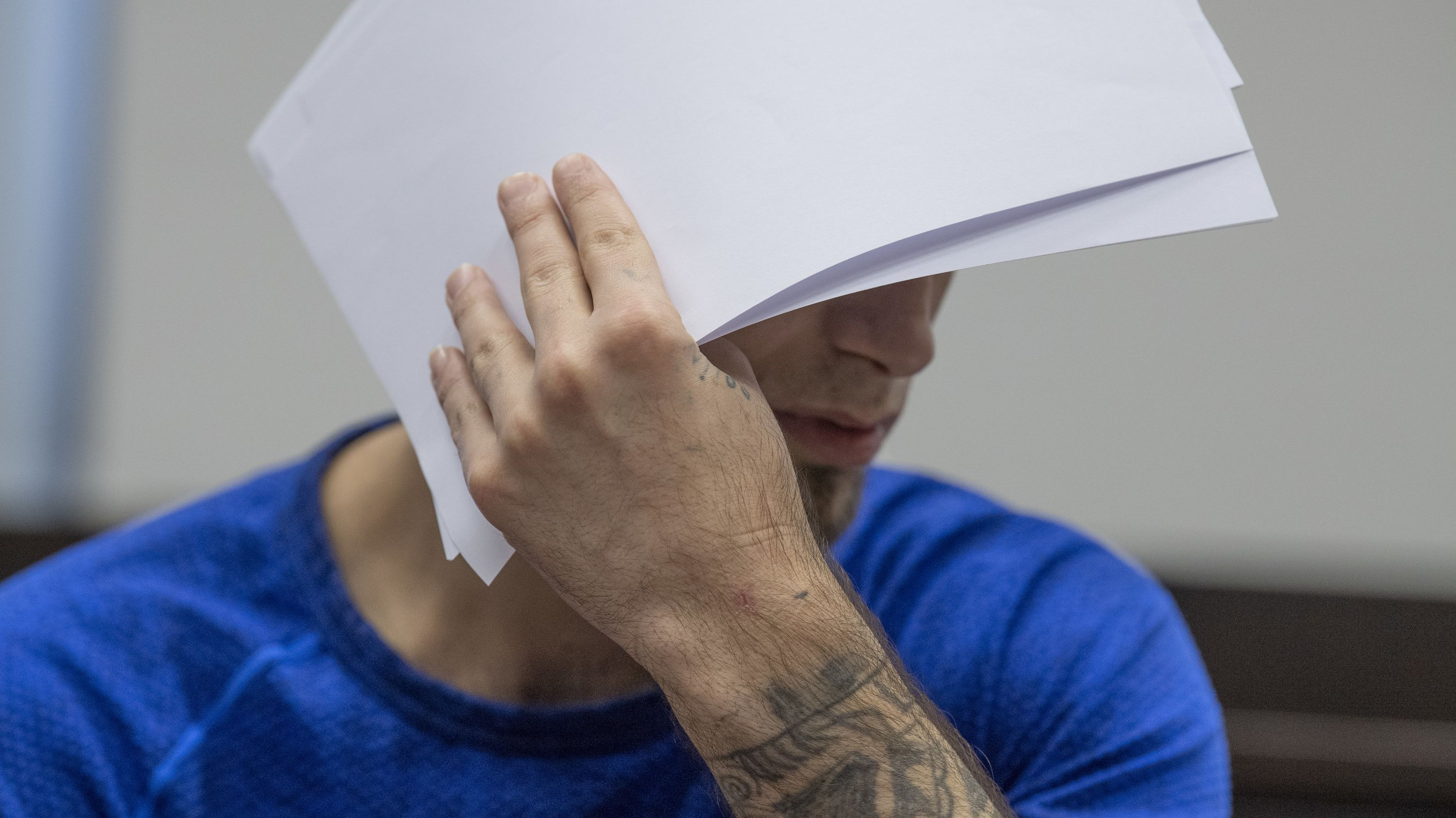 """26.06.2019: Ali B., Angeklagter im """"Mordfall Susanna"""", verdeckt beim Betreten des Verhandlungssaals sein Gesicht vor den Kameras der Fotografen"""