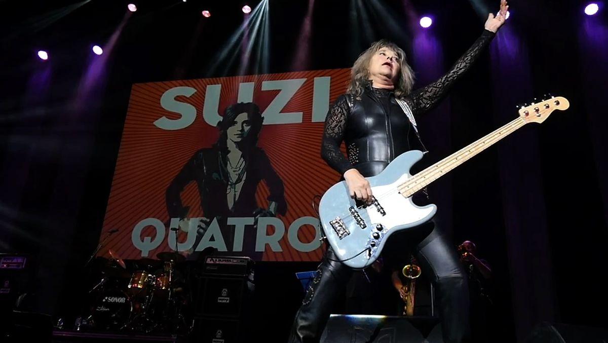 Live-Auftritt einer Frau mit E-Gitarre und Plakat im Hintergrund: Suzi Quatro