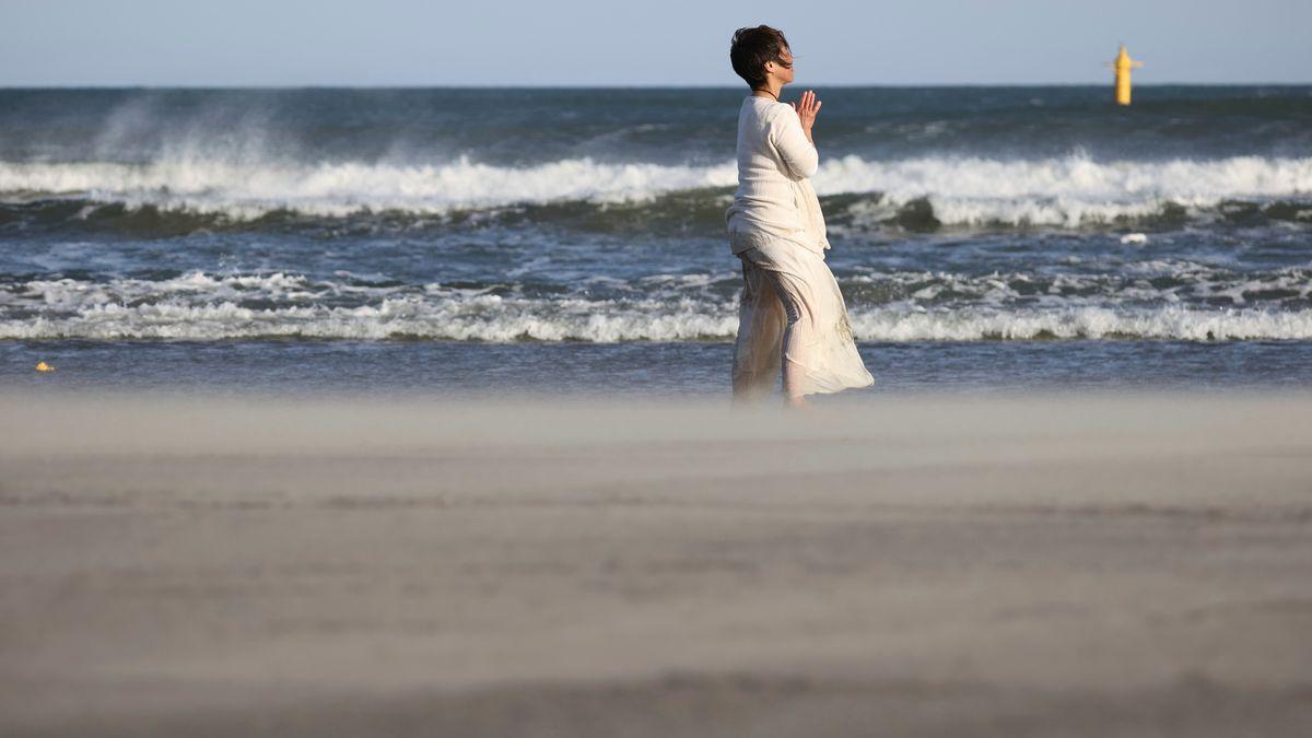 Eine Frau betet an einem Strand bei Fukushima (März 2021)