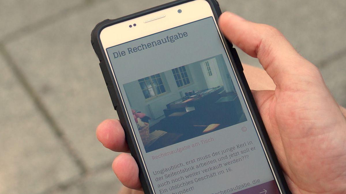 Mobiltelefon mit der App des Fugger- und Welsermuseums wird in der Hand gehalten