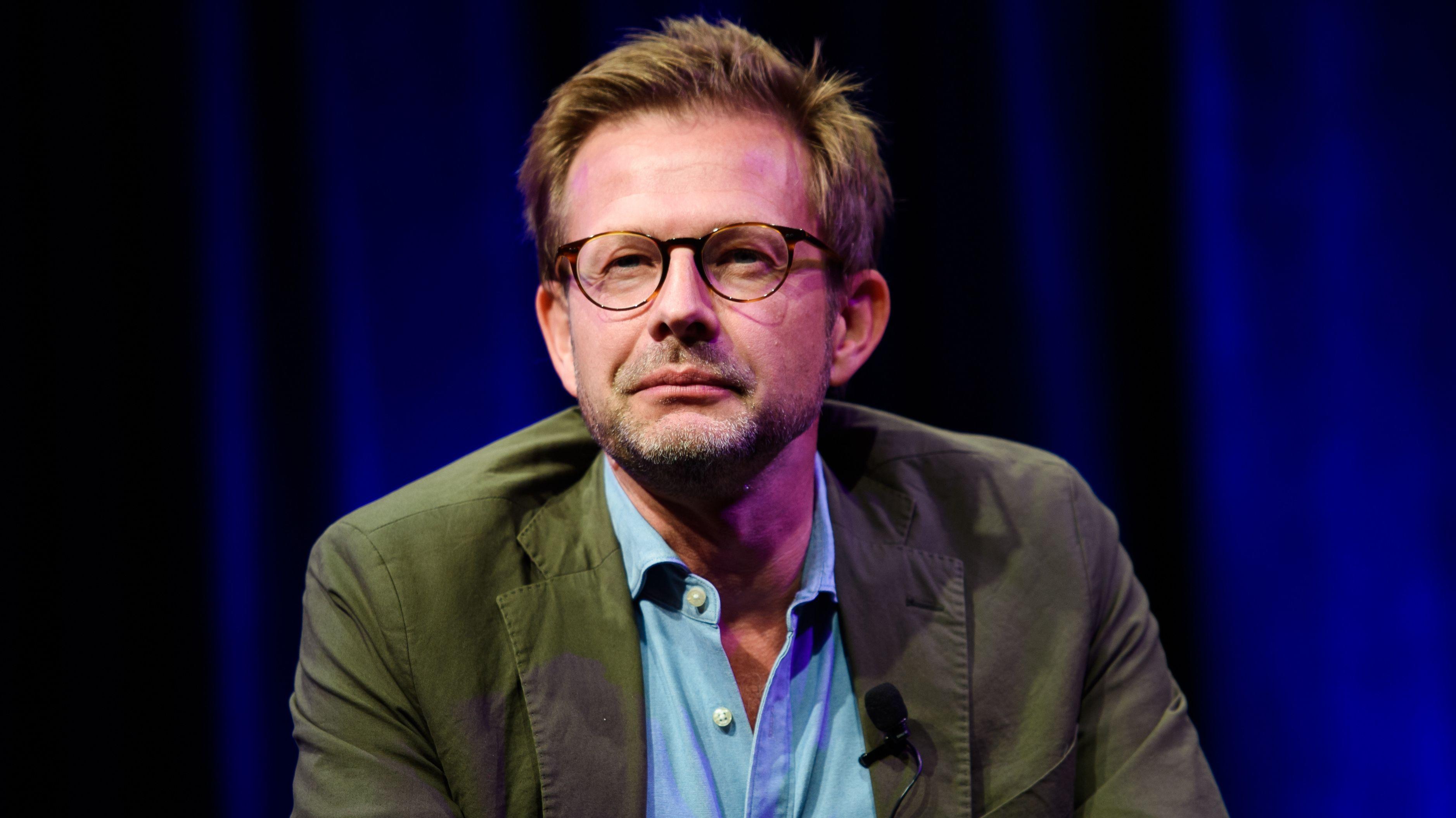 Florian Illies sitzt vor einem nachtblauen Vorhang und blickt mit zusammengekniffenen Augen in die Ferne