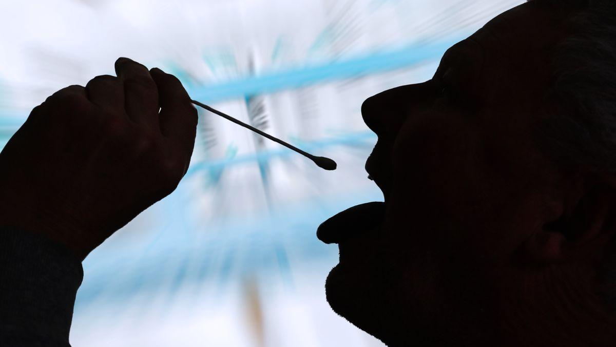 Ein Mann macht mit einem Wattestäbchen einen Selbsttest (Symbolbild)
