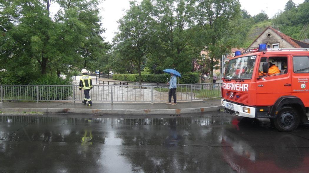 Knetzgau: Ein Fahrzeug der Feuerwehr, ein Feuerwehrmann, sowie ein Passant stehen auf einer Brücke im Landkreis Haßberge.