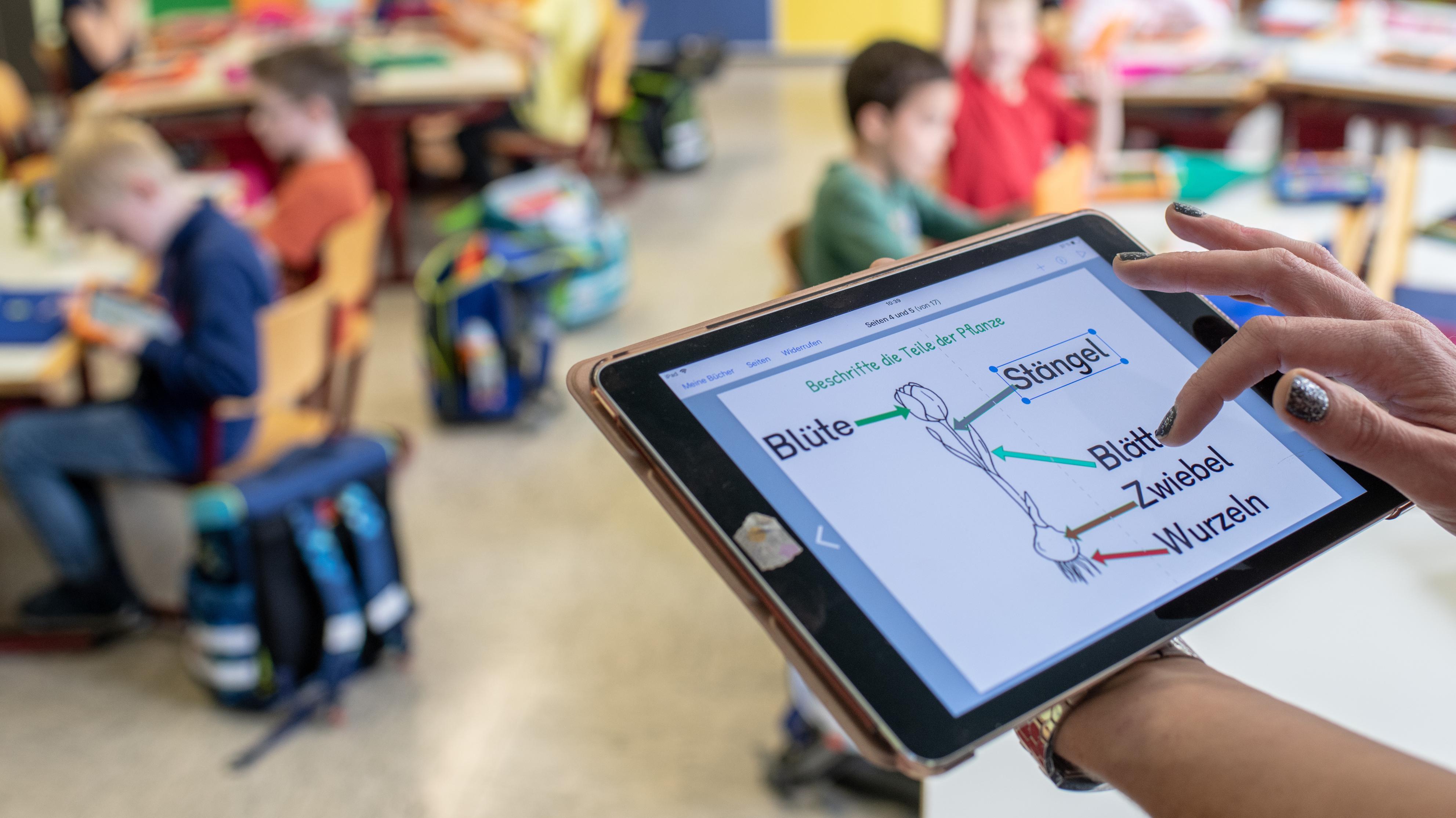 """Eine Lehrerin bedient in der Grundschule Offenstetten ein Tablet. Die Grundschule nimmt am Schulversuch """"Digitale Schule 2020"""" der Stiftung Bildungspakt Bayern teil. (Archivbild)"""