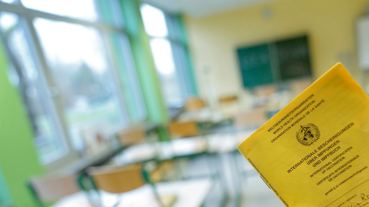 Impfpass mit Klassenzimmer einer Schule im Hintergrund (Symbolfoto)