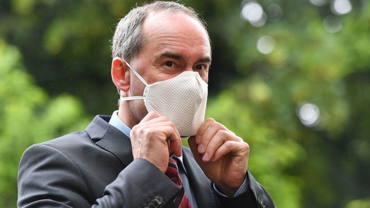 Hubert Aiwanger zeiht sich eine Schutzmaske an