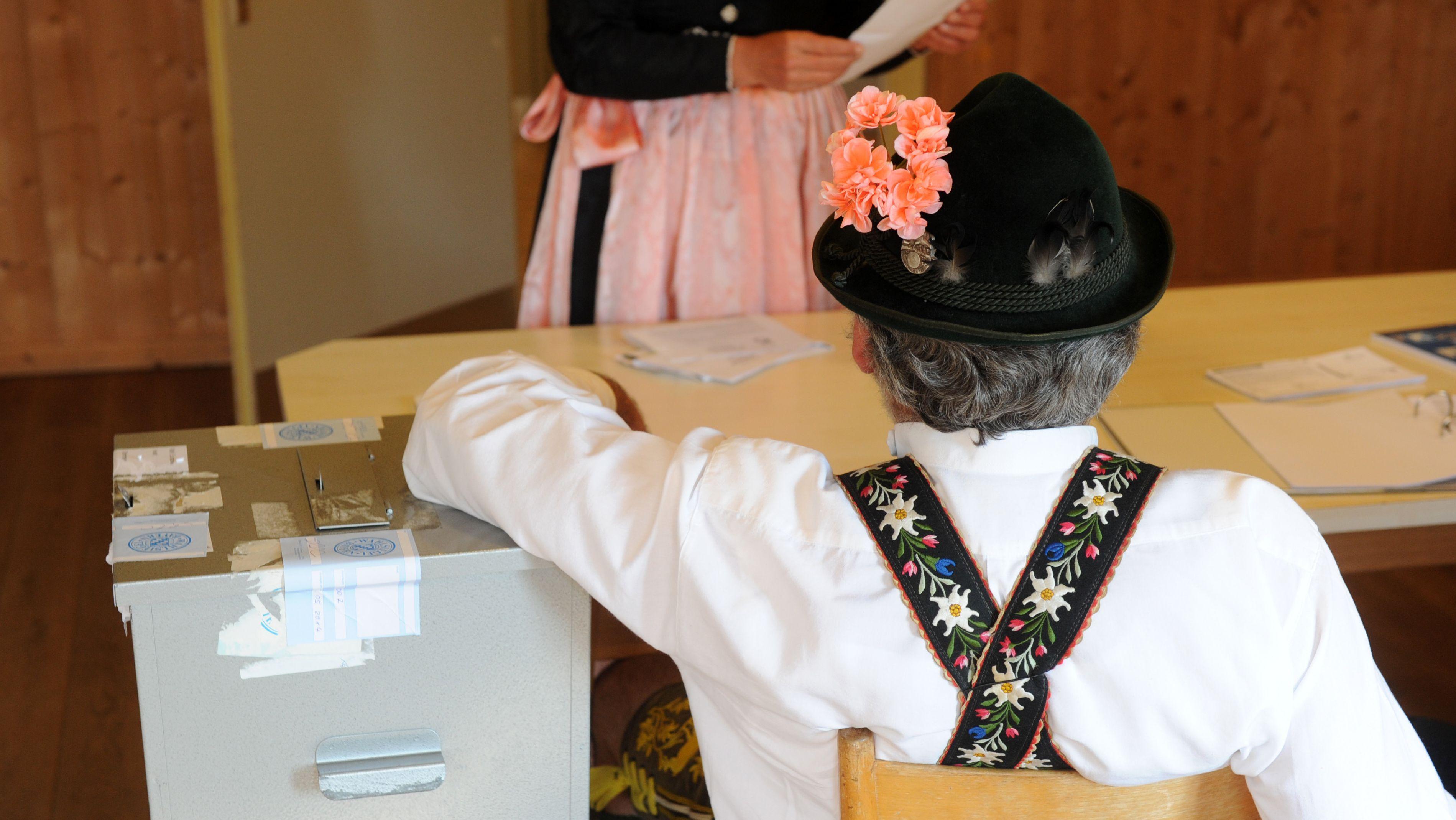 Ein Wahlhelfer in bayerischer Tracht mit Lederhose und Hut stützt sich in einem Wahllokal auf die Wahlurne.