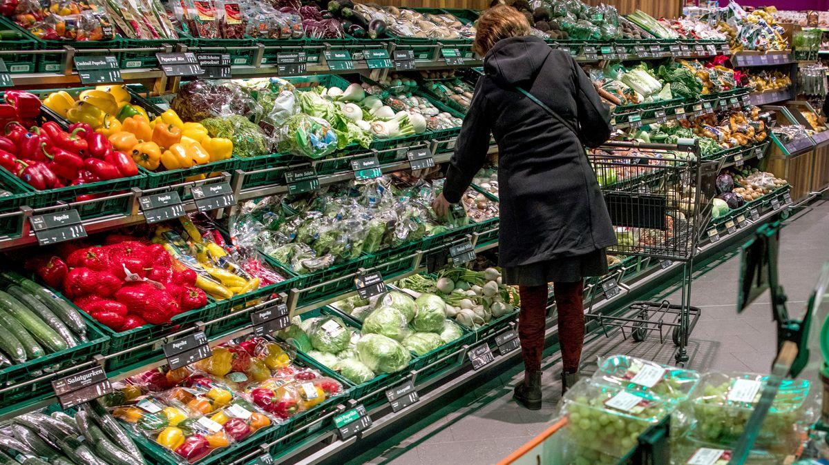 Ein Frau mit Einkaufswagen steht im Supermarkt vor der Gemüseauslage.