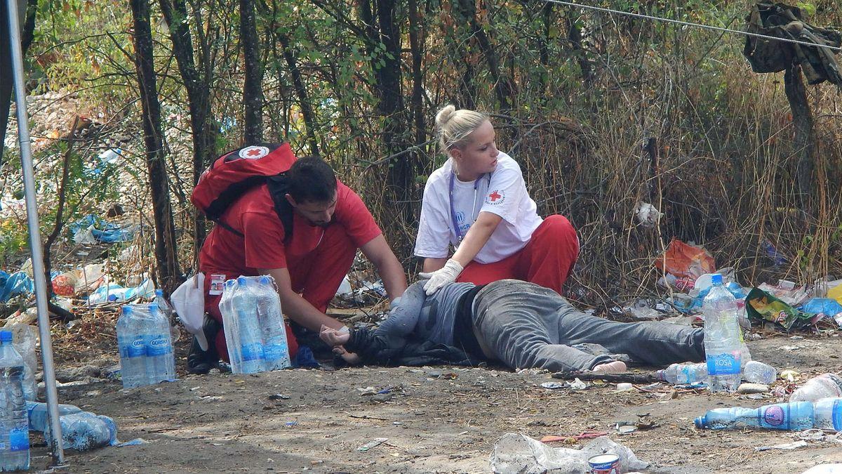 Team vom Roten Kreuz versorgt einen am Boden liegenden Mann