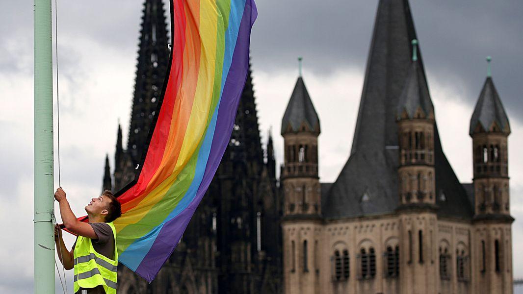 """Ein Arbeiter hängt 2017 nach der Entscheidung im Bundestag über die """"Ehe für alle"""" in Köln eine Regenbogenfahne auf."""