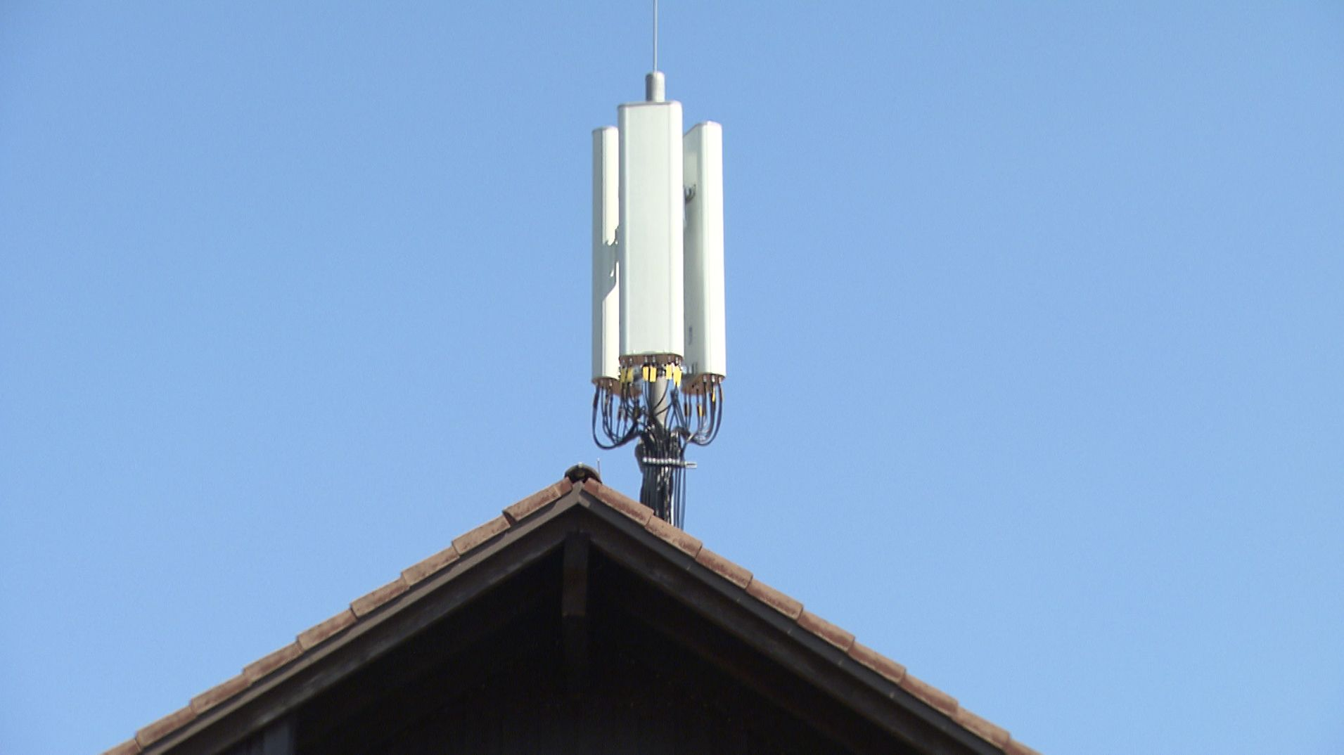 Eine Mobilfunkantenne auf einem Hausdach.