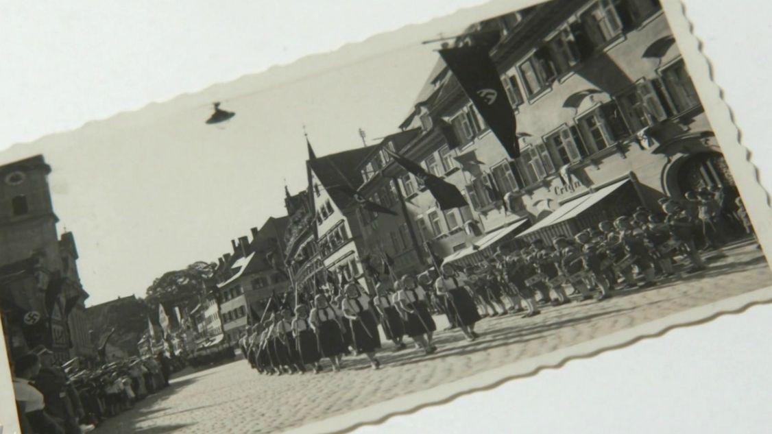 Auf einem Foto ist ein Umzug zu sehen: Frauen tragen Fahnen mit Hakenkreuzen. Auch an den Häusern sind Hakenkreuz-Fahnen befestigt.