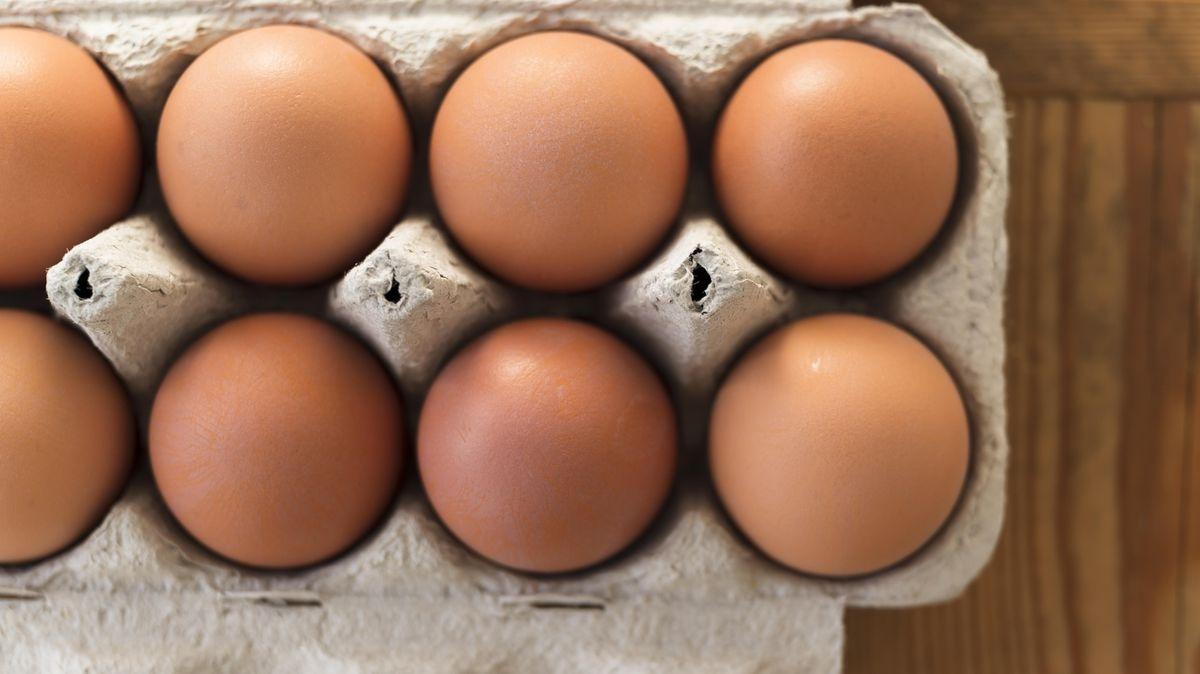 Eier in einer Kartonverpackung auf einem Holztisch
