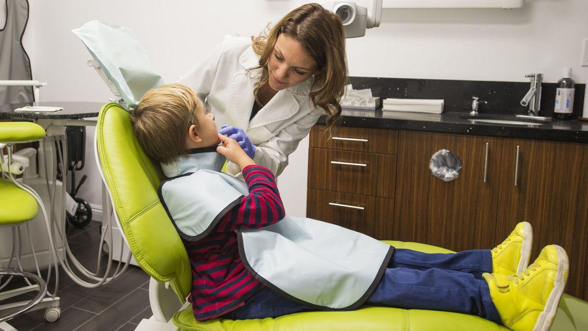 Ein Junge liegt auf einer Behandlungsliege, eine Zahnärztin schaut ihm in den Mund