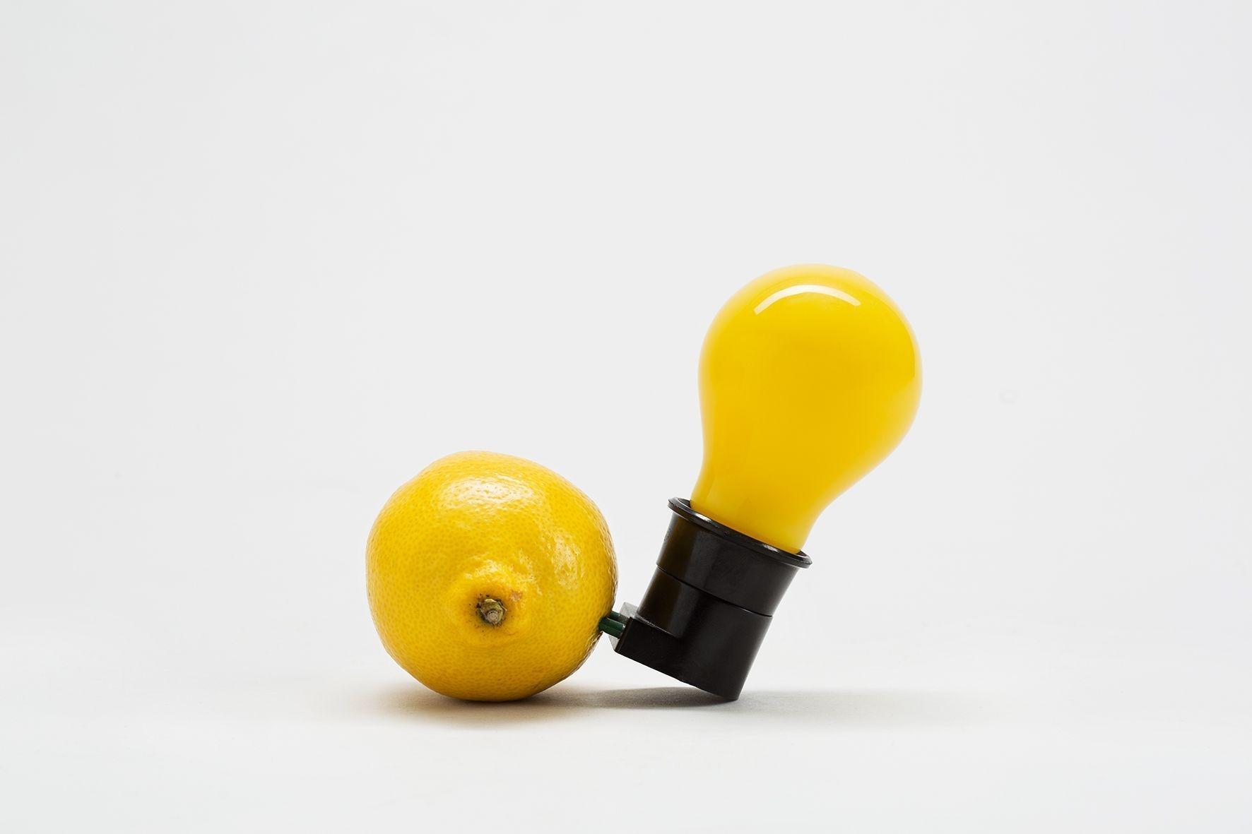 Gelbe Glühlampe in schwarzer Fassung deren Metallstifte in einer Zitrone stecken