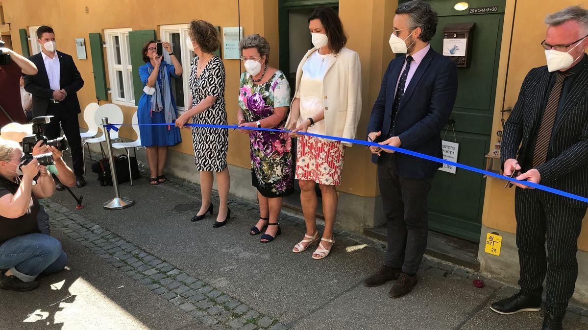 Unter anderem Ilse Aigner steht mit einer Schere vor einem Band vor dem neuen Museum in der Fuggerei