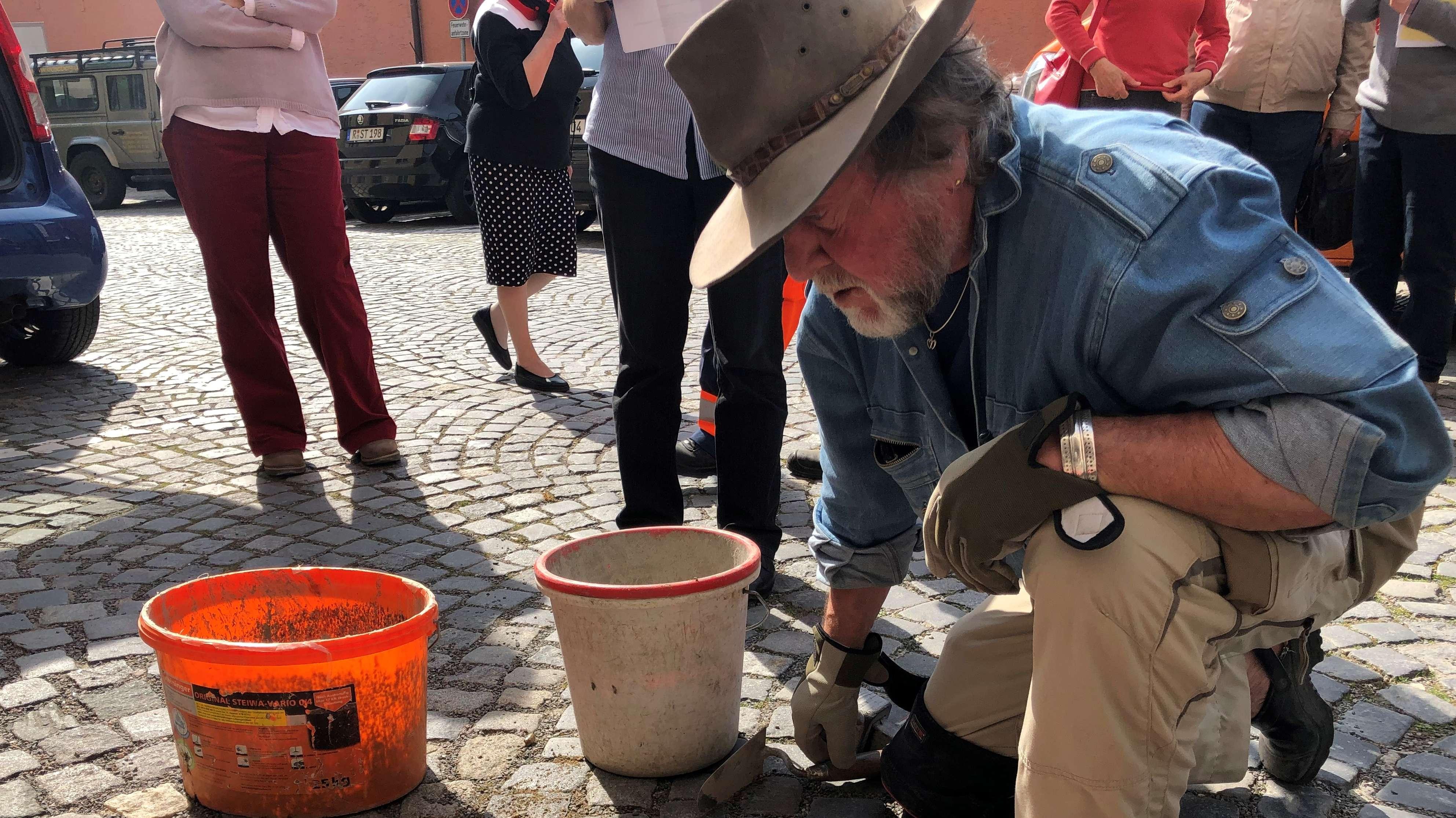 Der Künstler Gunter Demnig beim Verlegen eines Stolpersteins in Regensburg