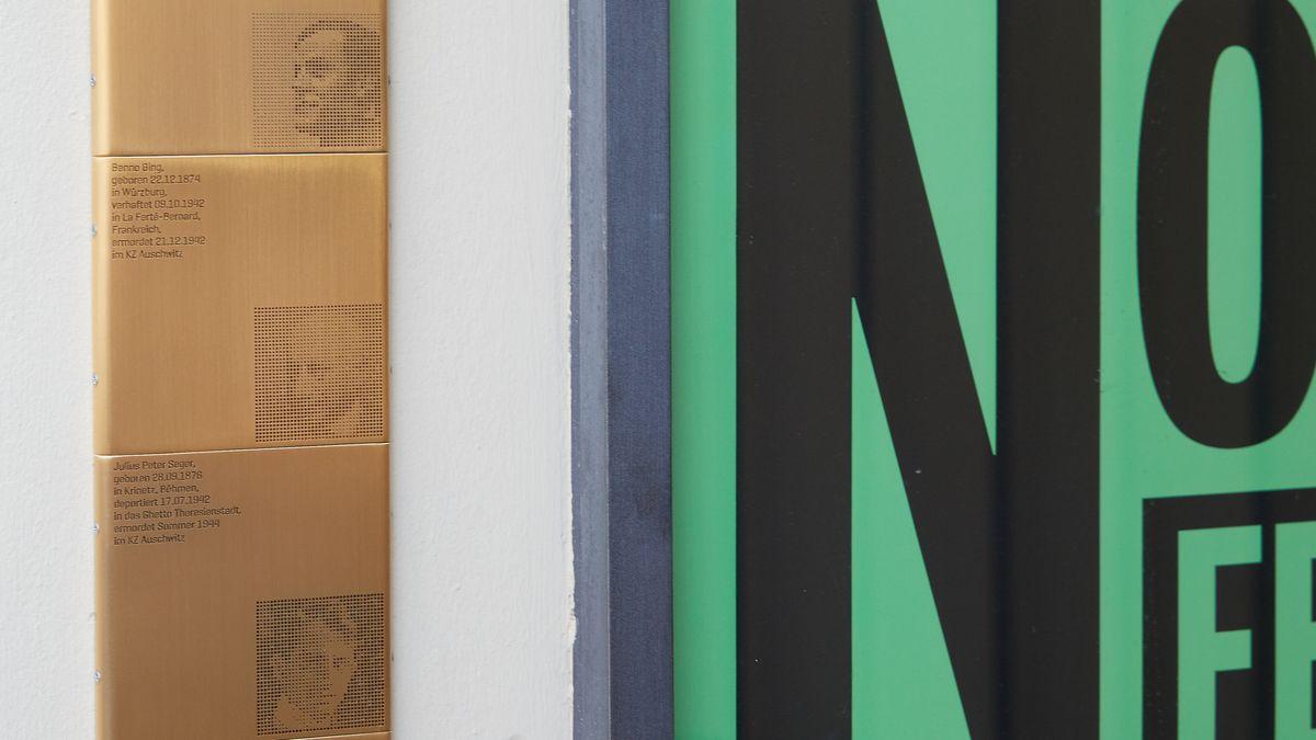 Erinnerungszeichen an den Kammerspielen, gestaltet von Kilian Stauss: Quadratische goldene Plaketten mit Porträts und Schrift neben einem großen Plakat mit schwarzer Schrift auf grünem Grund