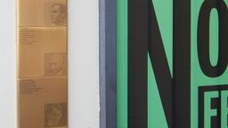 Erinnerungszeichen an den Kammerspielen, gestaltet von Kilian Stauss: Quadratische goldene Plaketten mit Porträts und Schrift neben einem großen Plakat mit schwarzer Schrift auf grünem Grund | Bild:Judith Buss