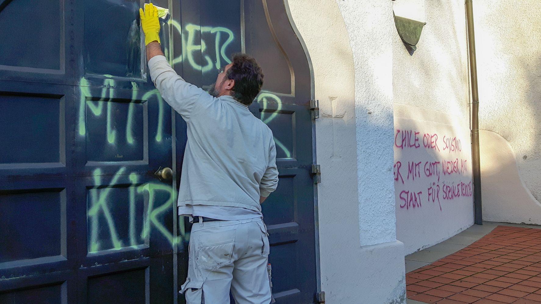 Ein Mann versucht, die Graffitis an der Eingangstür der St.-Georg-Kirche in Milbertshofen zu entfernen.