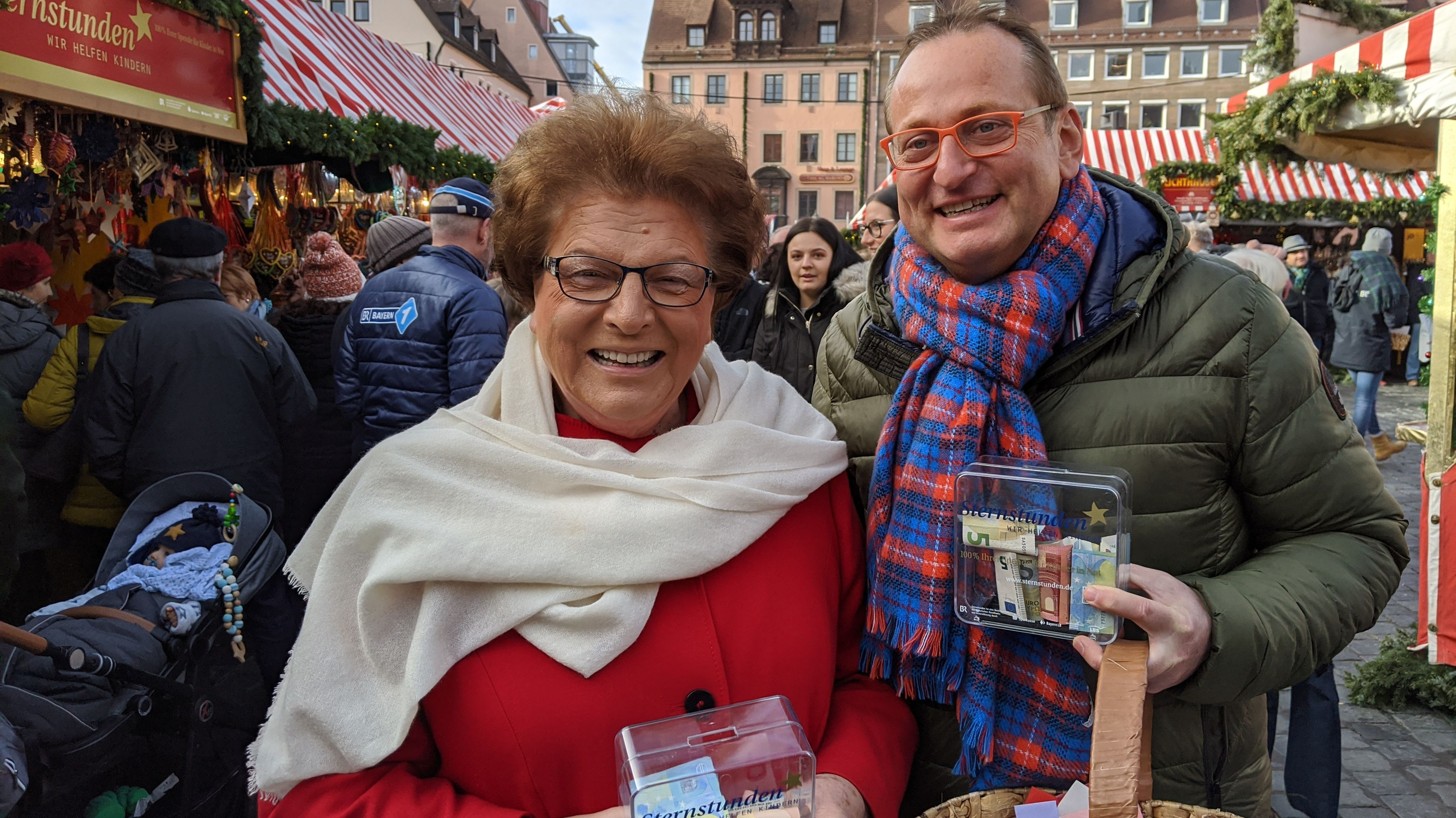 Barbara Stamm und Volker Heißmann stehen auf dem Christkindlesmarkt mit der Spendenbüchse in der Hand