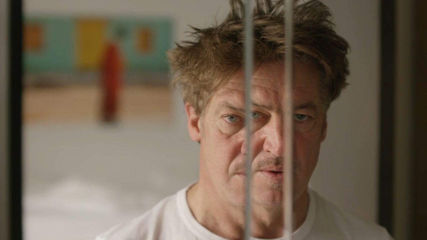 """Tobias Moretti in """"Baumbacher Syndrome"""": Der Schauspieler blickt in einen Spiegel, der sein Gesicht vervielfacht"""
