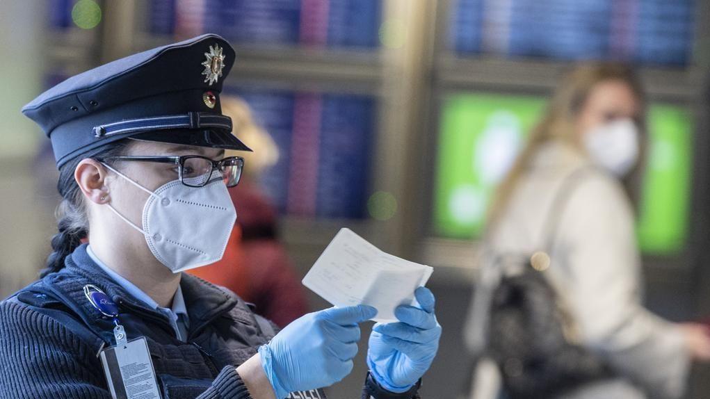 Eine Beamtin der Bundespolizei kontrolliert am Flughafen Frankfurt ein Dokument eines Passagiers.